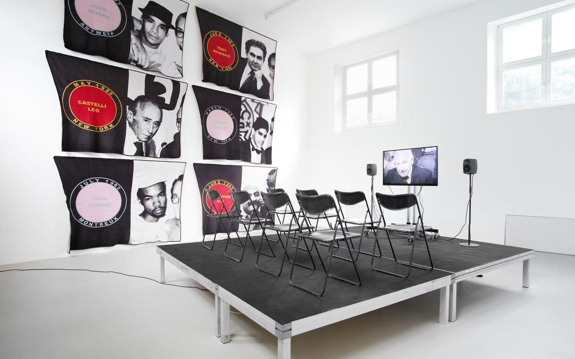 James Richards. Foreground: *Active Negative programme*. 2008. Video (color, sound). 20 min. Background: *Untitled Merchandise (Lovers & Dealers)*. 2012. Six machine-knitted nylon blankets. 152 x 228 cm. Installation view from *The Imaginary Museum,* Kunstverein Munich, 2012. Courtesy the artist and Rodeo, Istanbul and London and Cabinet, London