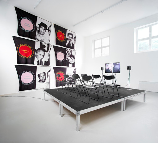 James Richards. Foreground: Active Negative programme. 2008. Video (color, sound). 20 min. Background: Untitled Merchandise (Lovers & Dealers). 2012. Six machine-knitted nylon blankets. 152 x 228 cm. Installation view from The Imaginary Museum, Kunstverein Munich, 2012. Courtesy the artist and Rodeo, Istanbul and London and Cabinet, London
