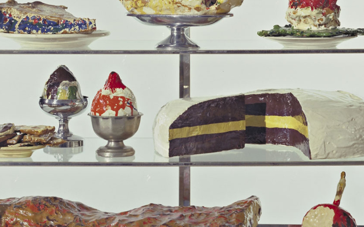 Claes Oldenburg. *Pastry Case, I.* 1961–62. Painted plaster sculptures on ceramic plates, metal platter, and cups in glass-and-metal case, 20 3/4 × 30 1/8 × 14 3/4″ (52.7 × 76.5 × 37.3 cm). The Museum of Modern Art, New York. The Sidney and Harriet Janis Collection. © 2012 Claes Oldenburg