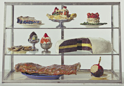 Claes Oldenburg. Pastry Case, I. 1961–62. Painted plaster sculptures on ceramic plates, metal platter, and cups in glass-and-metal case, 20 3/4 × 30 1/8 × 14 3/4″ (52.7 × 76.5 × 37.3 cm). The Museum of Modern Art, New York. The Sidney and Harriet Janis Collection. © 2012 Claes Oldenburg