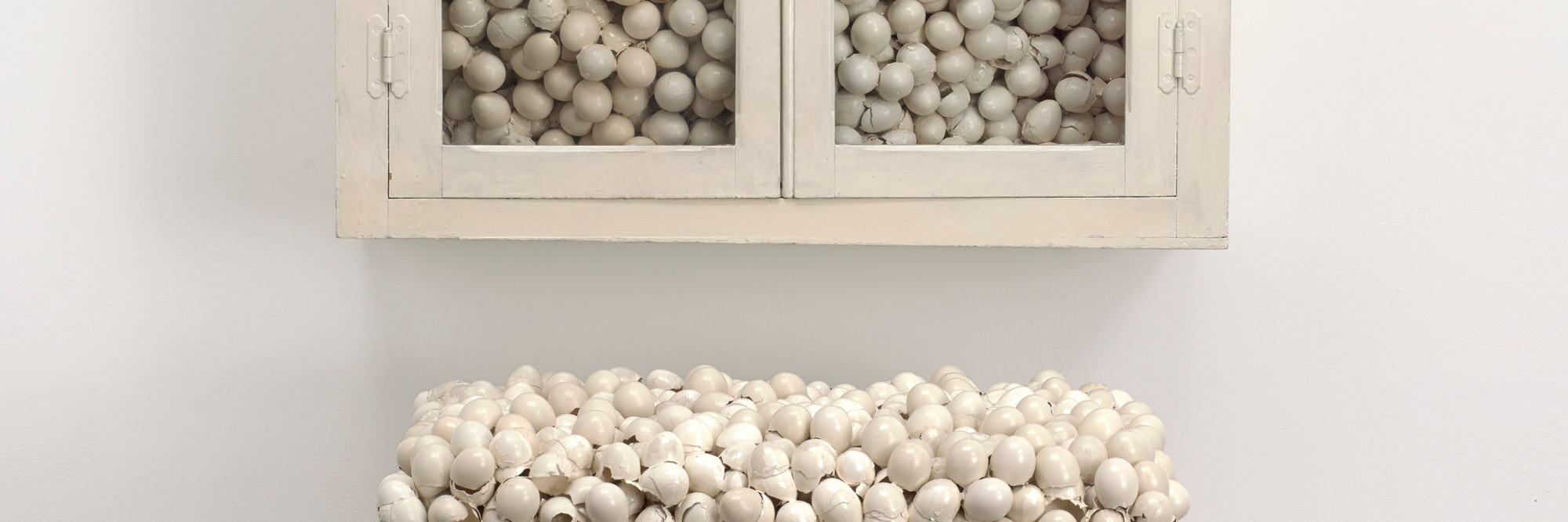 Marcel Broodthaers. Armoire blanche et table blanche (White Cabinet and White Table). 1965. Painted cabinet, table, and eggshells; cabinet 33 7/8 × 32 1/4 × 24 1/2″ (86 × 82 × 62 cm), table 41 × 39 3/8 × 15 3/4″ (104 × 100 × 40 cm). The Museum of Modern Art, New York. Fractional and promised gift of Jo Carole and Ronald S. Lauder. © 2015 Estate of Marcel Broodthaers/Artists Rights Society (ARS), New York/SABAM, Brussels