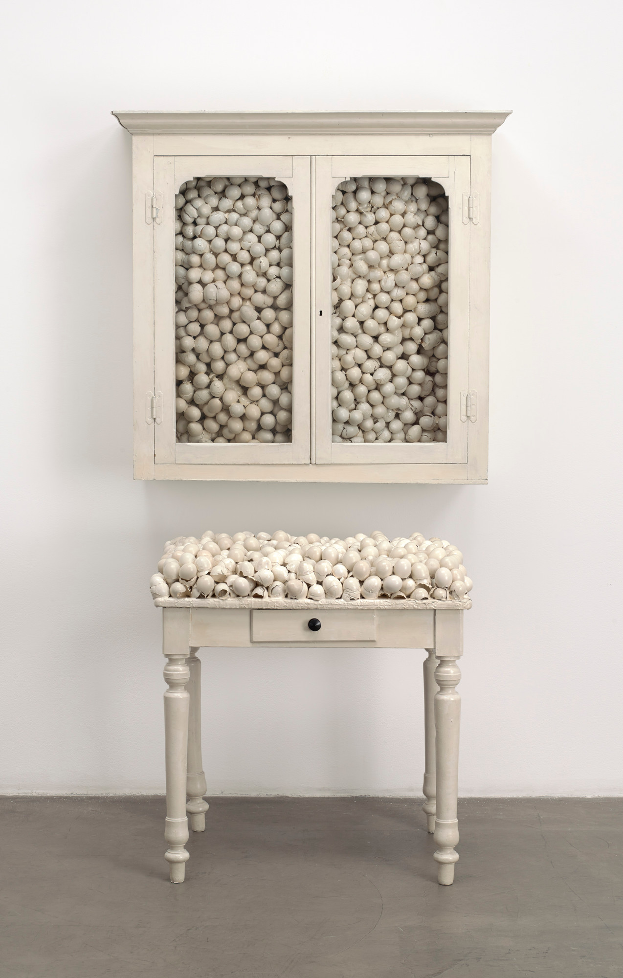 Marcel Broodthaers. Armoire blanche et table blanche (White Cabinet and White Table). 1965. Painted cabinet, table, and eggshells; cabinet 33 7⁄8 × 32 1⁄4 × 24 1/2″ (86 × 82 × 62 cm), table 41 × 39 3⁄8 × 15 3/4″ (104 × 100 × 40 cm). The Museum of Modern Art, New York. Fractional and promised gift of Jo Carole and Ronald S. Lauder. © 2015 Estate of Marcel Broodthaers/Artists Rights Society (ARS), New York/SABAM, Brussels