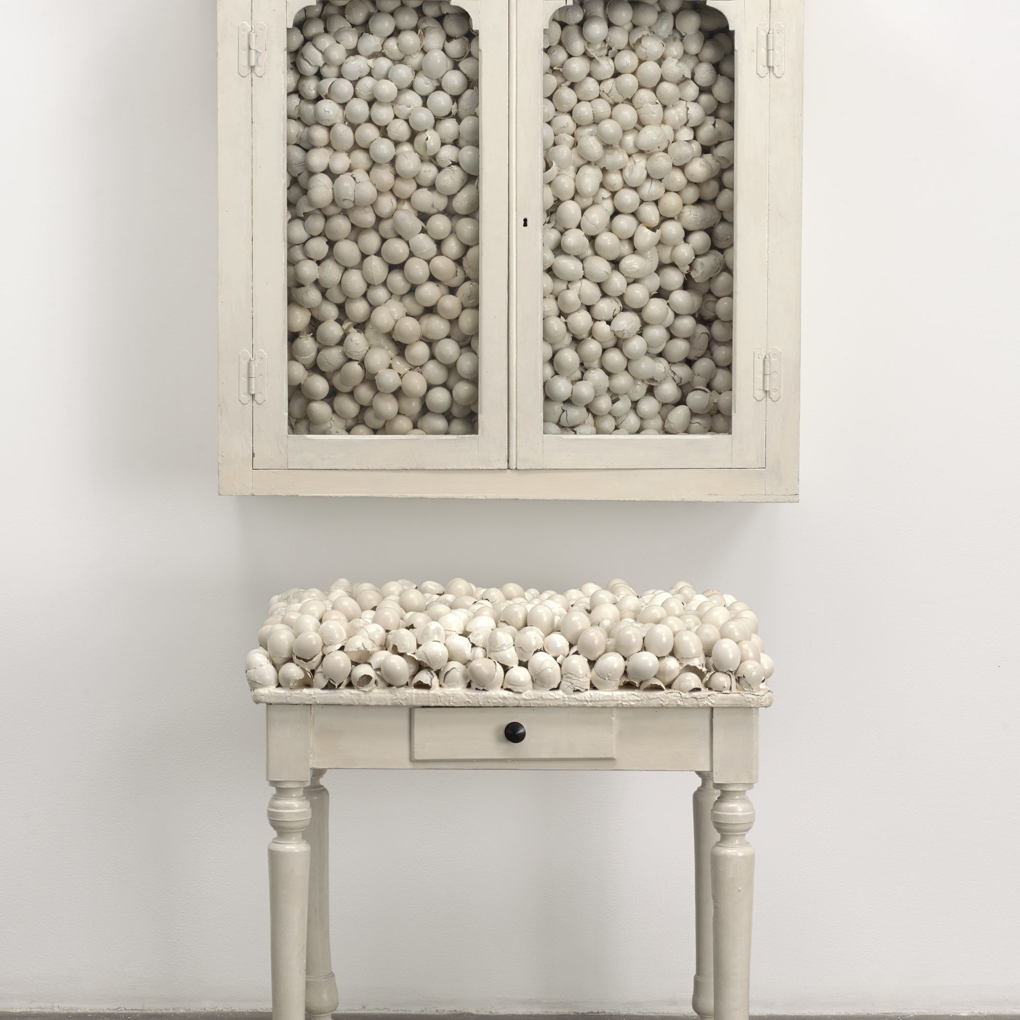 Marcel Broodthaers. Armoire blanche et table blanche (White Cabinet and White Table). 1965. Painted cabinet, table, and eggshells; cabinet 33 7/8 x 32 1/4 x 24 1/2″ (86 x 82 x 62 cm), table 41 x 39 3/8 x 15 3/4″ (104 x 100 x 40 cm). The Museum of Modern Art, New York. Fractional and promised gift of Jo Carole and Ronald S. Lauder. © 2015 Estate of Marcel Broodthaers/Artists Rights Society (ARS), New York/SABAM, Brussels