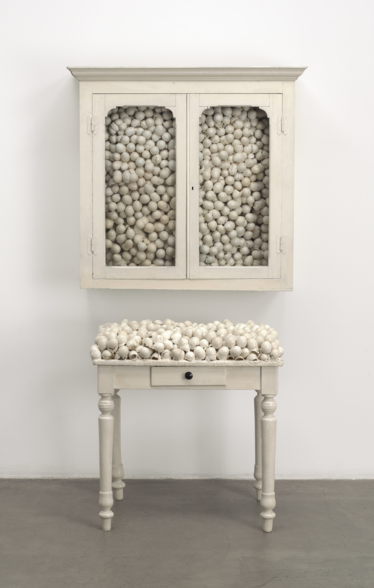 Marcel Broodthaers (Belgian, 1924–1976). Armoire blanche et table blanche (White cabinet and white table). 1965. Painted furniture with eggshells, cabinet: 33 7/8 × 32 1/4 × 24 1/2 in. (86 × 82 × 62 cm); table: 41 × 39 3/8 × 15 3/4 in. (104 × 100 × 40 cm). The Museum of Modern Art, New York. Fractional and promised gift of Jo Carole and Ronald S. Lauder, 1992. © 2016 Estate of Marcel Broodthaers / Artists Rights Society (ARS), New York / SABAM, Brussels