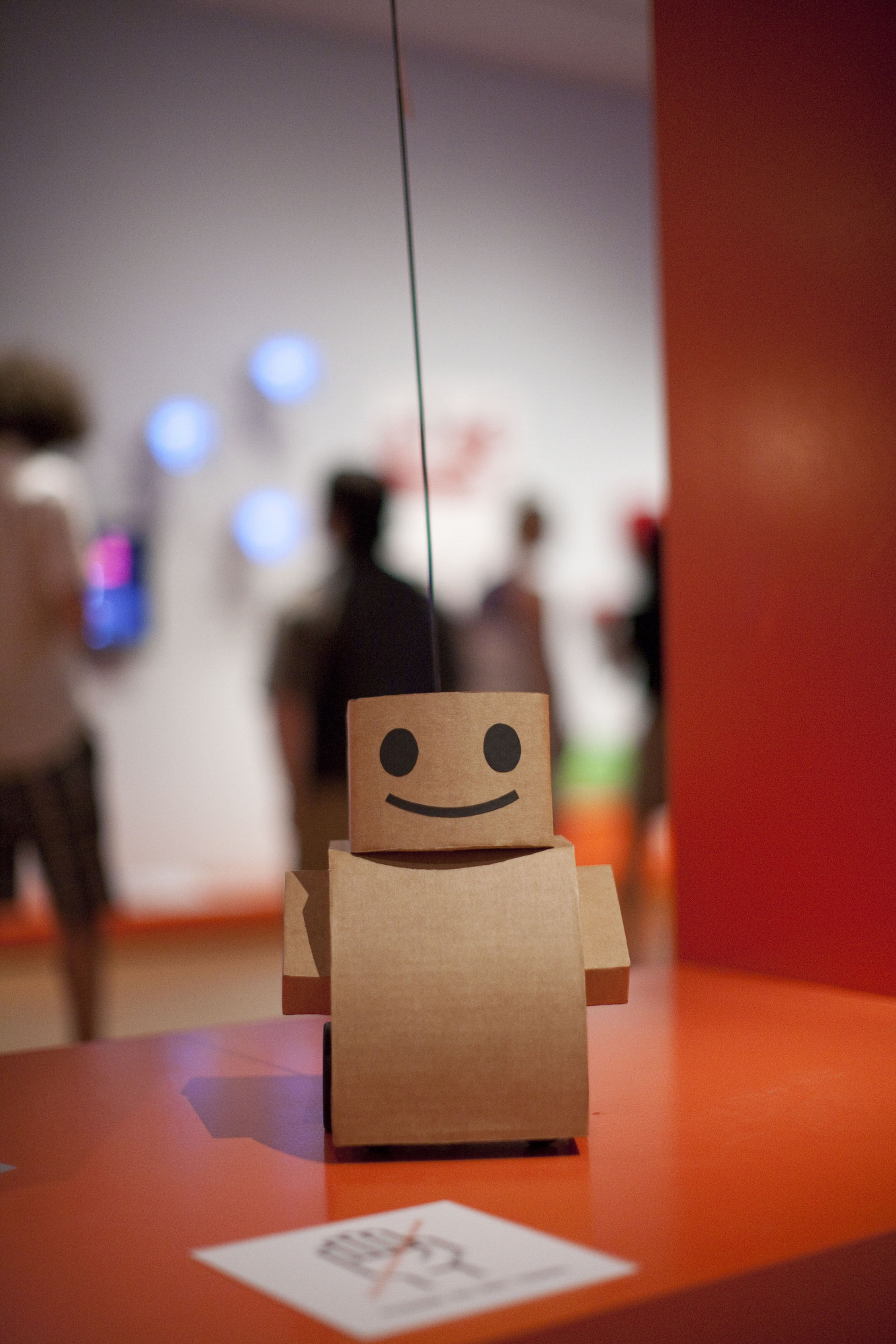 "Kacie Kinzer. Interactive Telecommunications Program, Tisch School of the Arts, New York University. Tweenbot. 2009. Cardboard, paper, ink, batteries, motor, and wheels, 36 x 8 1/2 x 14"" (91.4 x 21.6 x 35.6 cm). Installation view at The Museum of Modern Art, 2011. Photo © Scott Rudd"