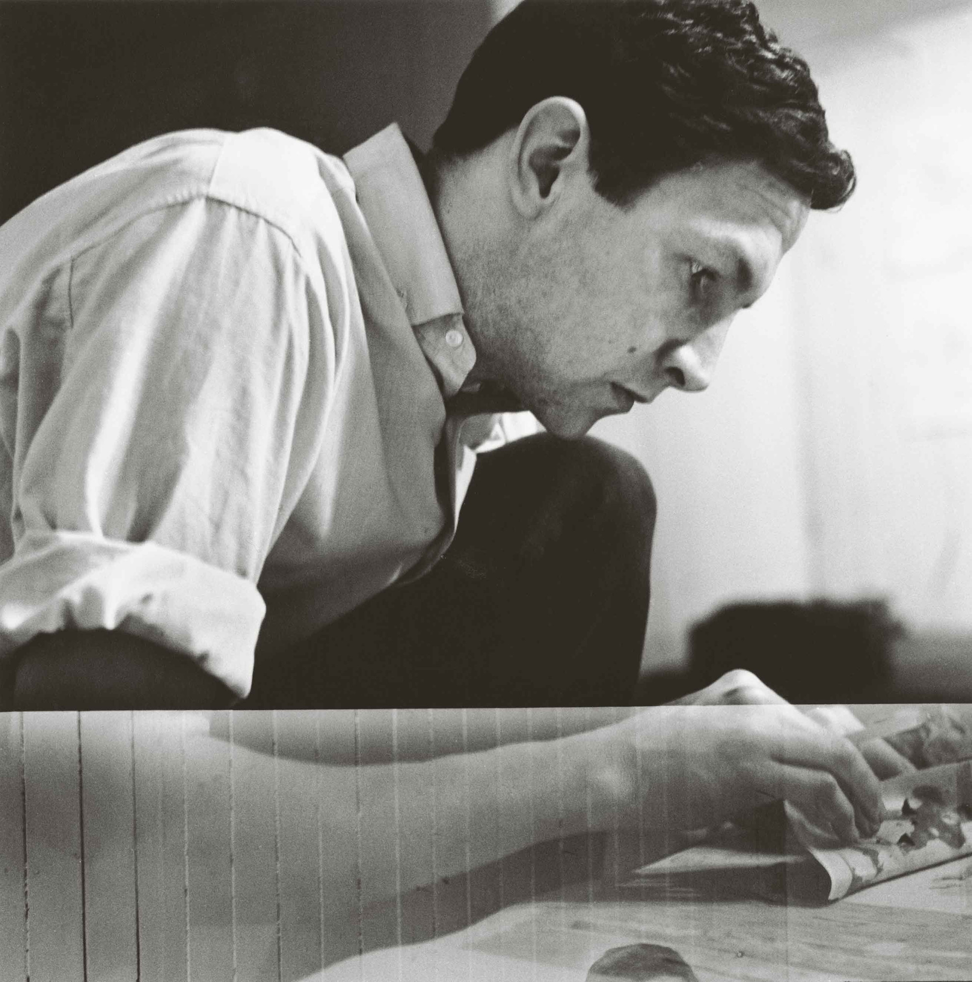 Rauschenberg working on a solvent transfer drawing in his Front Street studio, New York, 1958. Photograph: Jasper Johns. Photograph Collection. Robert Rauschenberg Foundation Archives, New York