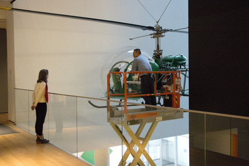 Artist Nina Katchadourian watches the dusting of the helicopter. Shown: Arthur Young. Bell-47D1 Helicopter. 1945. Manufacturer: Bell Helicopter Inc., Buffalo, NY. Aluminum, steel, and acrylic plastic, 9′ 2 3/4″ × 7′ 11″ × 42′ 8 3/4″ (281.3 × 302 × 1271.9 cm). Marshall Cogan Purchase Fund. Photo: Manuel Martagon. © 2016 The Museum of Modern Art