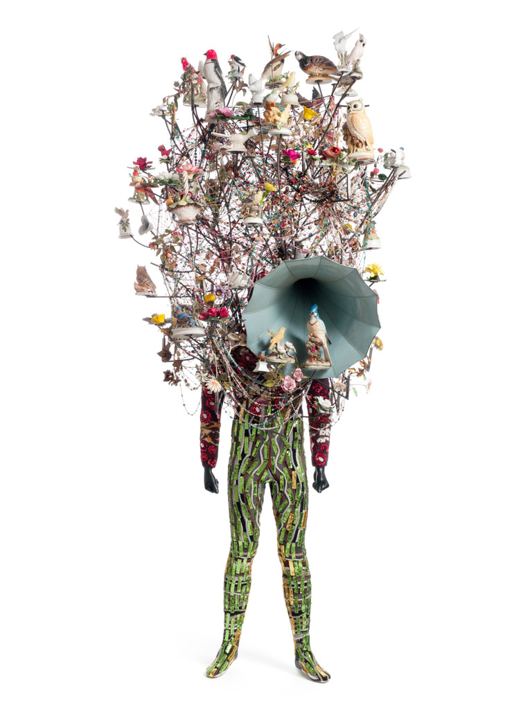 "Nick Cave. _Soundsuit_. 2011. Found objects, knit head and bodysuit, and mannequin, 10' 1"" x 42"" x 33"" (307.3 x 106.7 x 83.8 cm). The Museum of Modern Art, New York. Gift of Agnes Gund in honor of Dr. Stuart W. Lewis. © 2018 Nick Cave. Photo:  Imaging and Visual Resources Department, MoMA"
