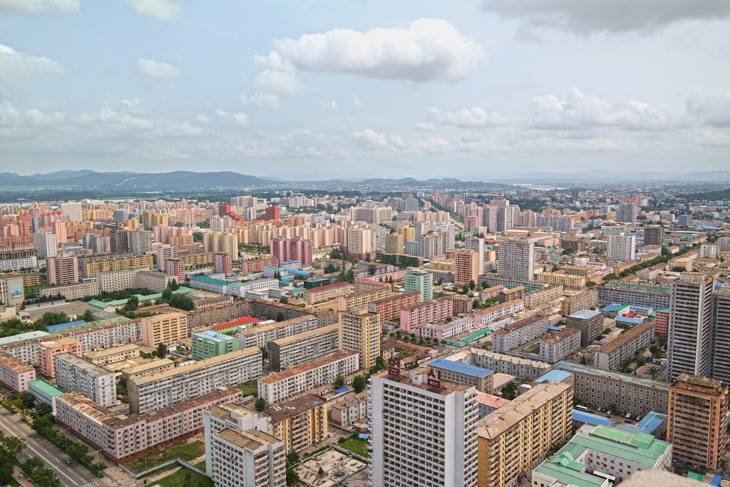 View  from  the  top  of  the  Tower  of  the  Juche  Idea  in  Pyongyang.  The  North    Korean  capital  stretches  out  beneath  you  as  a  pastel-colored  panorama,  a  rolling  field  of  tower  blocks  painted  in  terracotta  and  yellow  ochre,  turquoise  and  baby  blue—a  distinctive  color  palette  that  recurs  throughout  the  country's  architecture  and  interiors. © Oliver  Wainwright