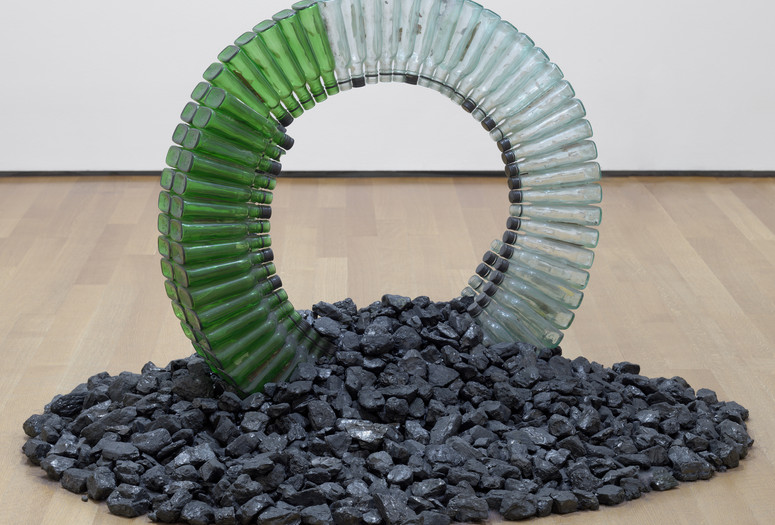 "David Hammons. Untitled (Night Train). 1989. Glass bottles, caps, silicone glue, and coal, dimensions variable, approximately 30 x 42 x 42"" (76.2 x 106.7 x 106.7 cm). Gift of the Hudgins Family in memory of Lawrence D. ""Butch"" Morris"
