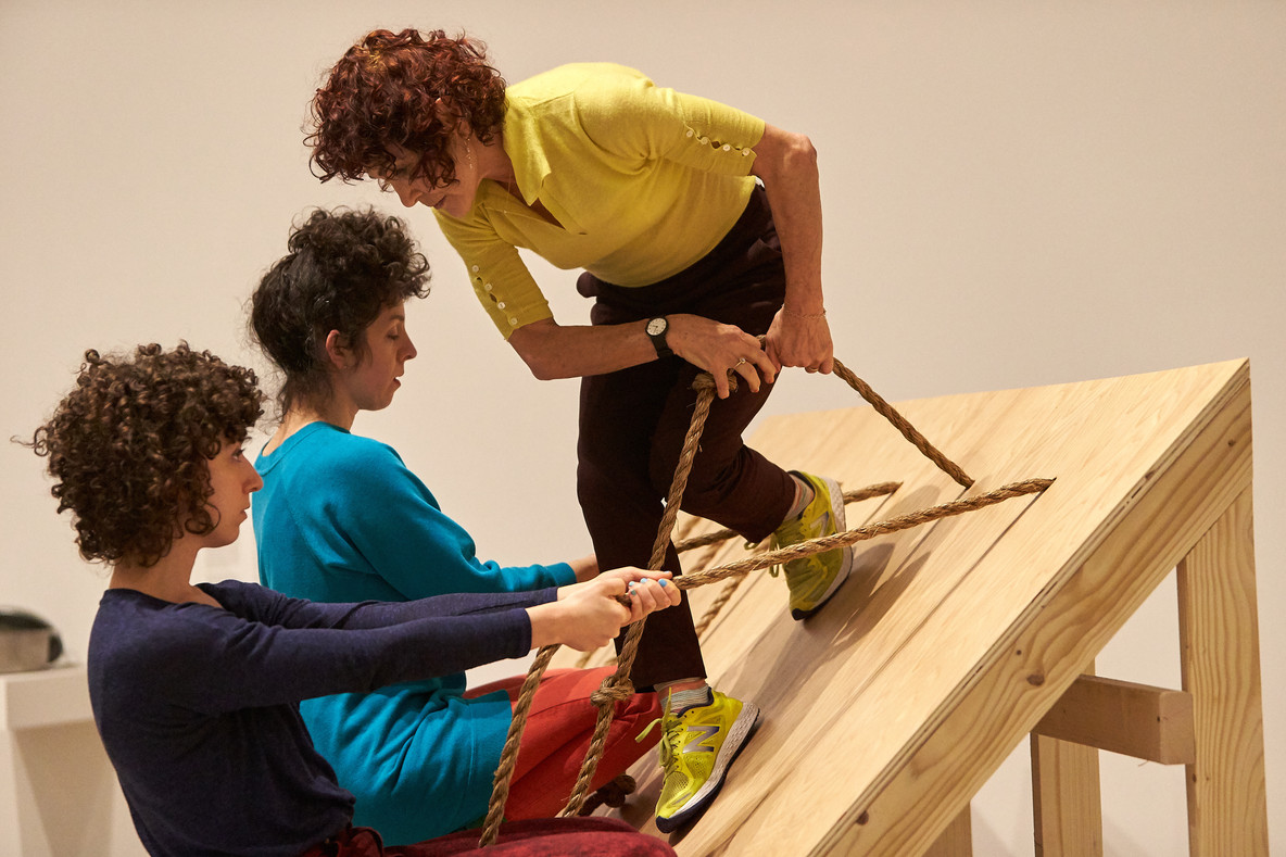 Slant Board features a 45-degree wooden incline with ropes fastened along the top. Left to right, Talya Epstein, Lee Relvas, and Jody Oberfelder brace themselves with the ropes and move across the board, navigating one another's presence. Occasionally, the performers rest, standing or crouching while bracing themselves with the ropes.