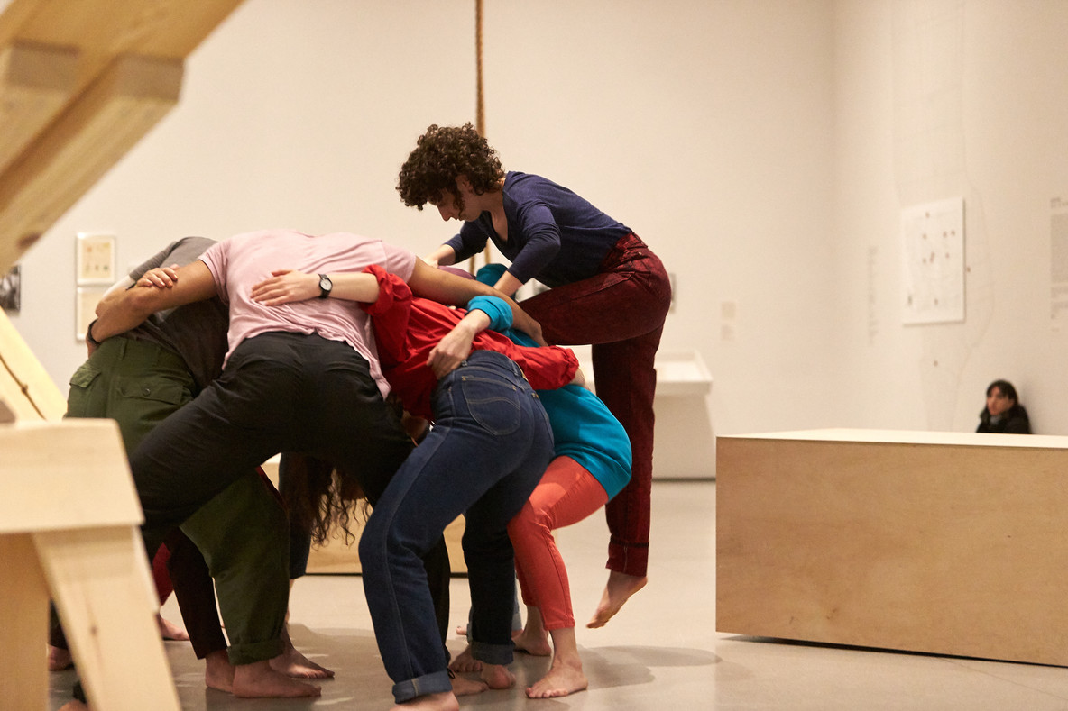 Huddle is a continually shifting mass of bodies. Seven to nine performers create a solid base and take turns climbing over the group. In doing this, they create a sculptural form Forti has often described as a mountain.
