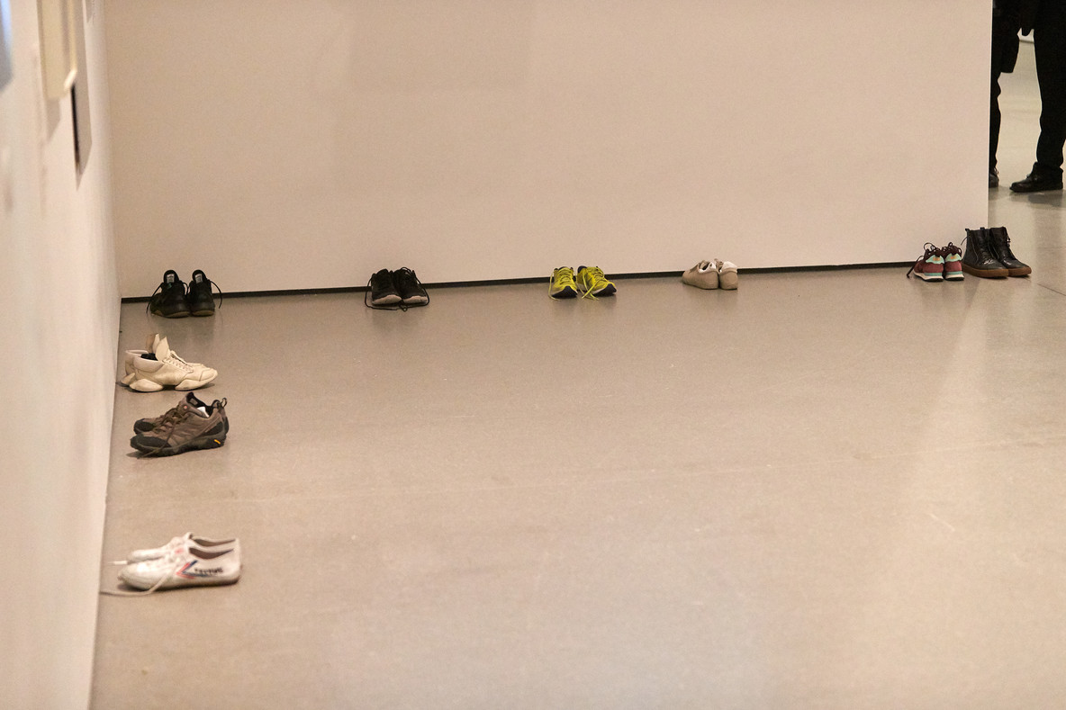The performers place their shoes in the corner of the gallery and prepare for the first performance, Huddle.