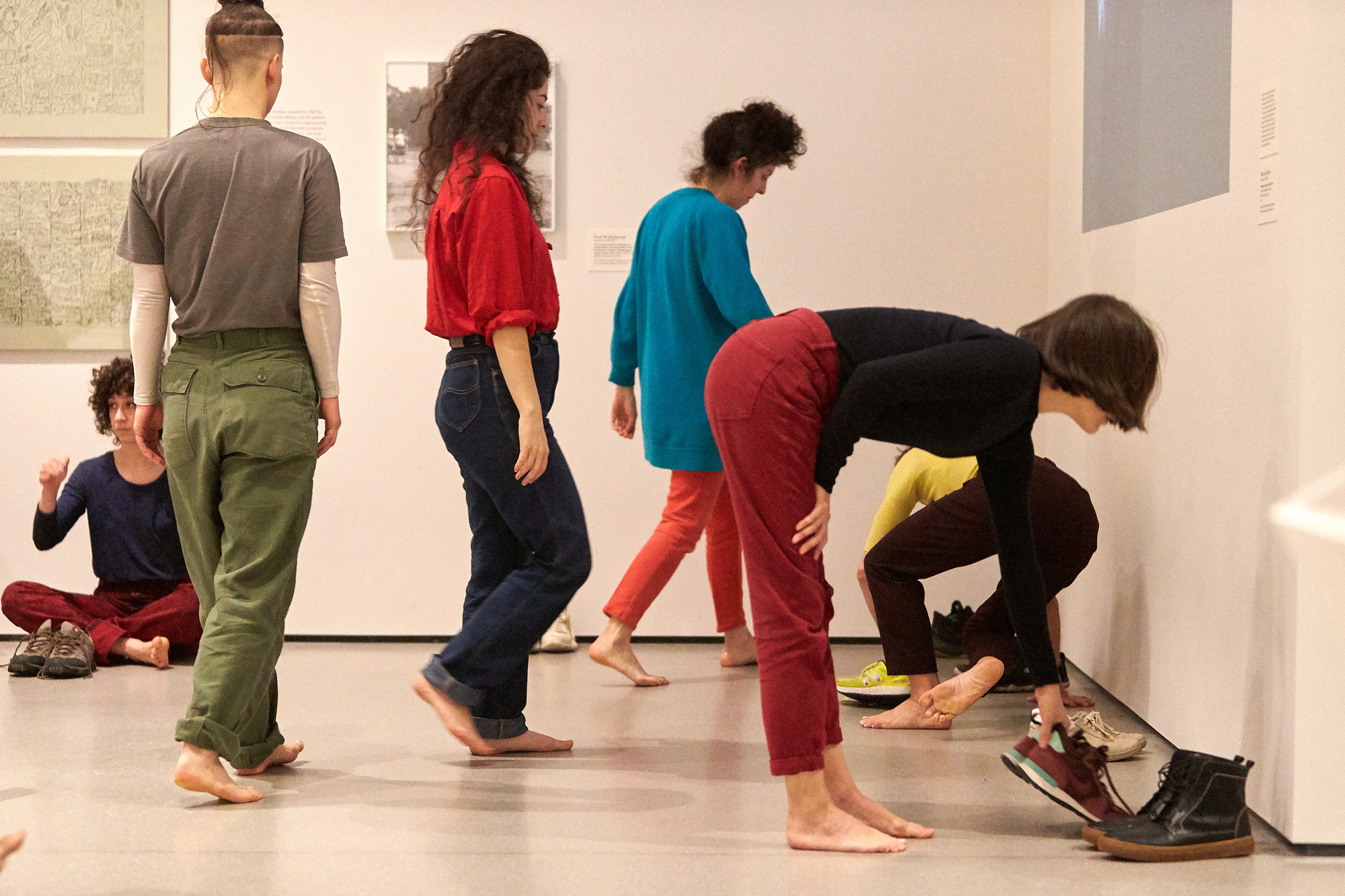 While Huddle is intended to be performed in bare feet, the other Dance Constructions are performed in tennis shoes. Here, the performers put on their shoes and prepare for the remainder of the works.