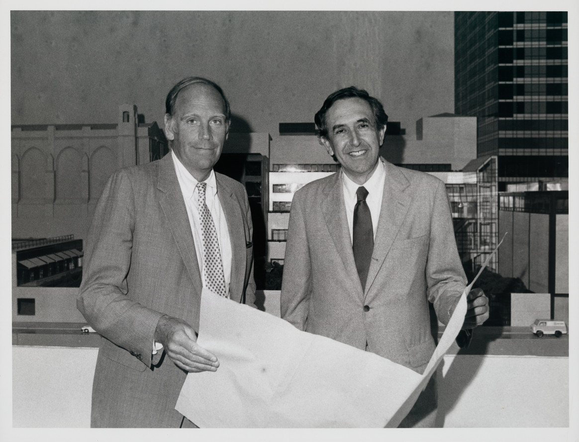 MoMA director Richard Oldenburg (left) and architect César Pelli with a model of the new building in the background, summer 1983