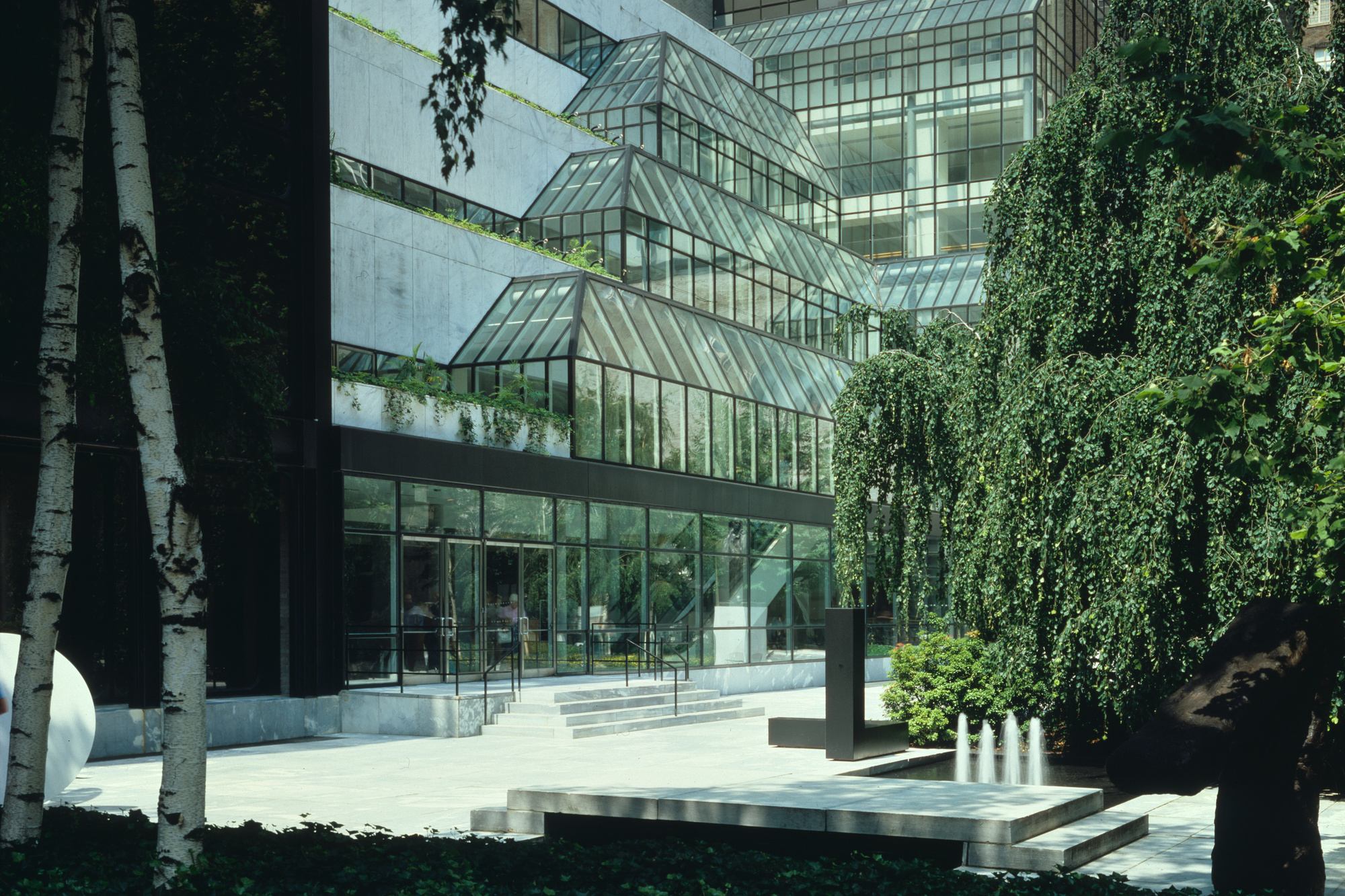 "Foreground: The Abby Aldrich Rockefeller Sculpture Garden, designed in 1953 by Philip Johnson; Background: Garden Hall, designed in 1984, and Museum Tower, designed in 1982, by César Pelli & Associates. Color transparency, 4 × 5"" (10.1 × 12.7 cm). Photographic Archive. The Museum of Modern Art Archives, New York. © The Museum of Modern Art, New York. Photo: Scott Frances"