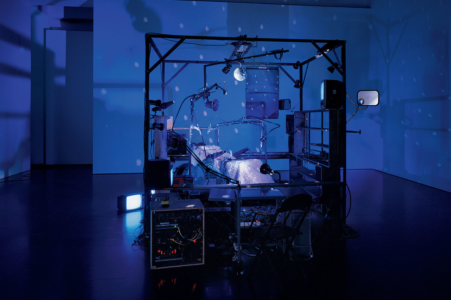 Janet Cardiff and George Bures Miller. The Killing Machine. 2007. Pneumatics, robotics, electromagnetic beaters, dentist chair, electric guitar, CRT monitors, computer, various control systems, lights, and sound (approx. 5 min.). 9′ 10″ x 13′ 1″ x 8′ 2″ (118 x 157 x 98 cm). The Museum of Modern Art, New York. Gift of the Julia Stoschek Foundation, Düsseldorf, and the Dunn Bequest. © 2019 Janet Cardiff and George Bures Miller. Photo: Seber Ugarte & Lorena López. Courtesy the artists and Luhring Augustine, New York.