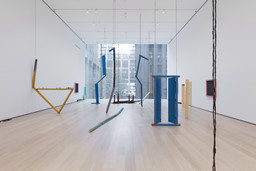 Sheela Gowda. Of All People. 2011. Wood doors, shutters, doorframes, windows, pillars, table and fragments, framed photographs, wood chips, and metal chains, overall dimensions variable. Committee on Painting and Sculpture Funds. © 2019 Sheela Gowda. Installation view, The Museum of Modern Art, New York, 2019. Digital Image © 2019 MoMA, NY. Photo: John Wronn