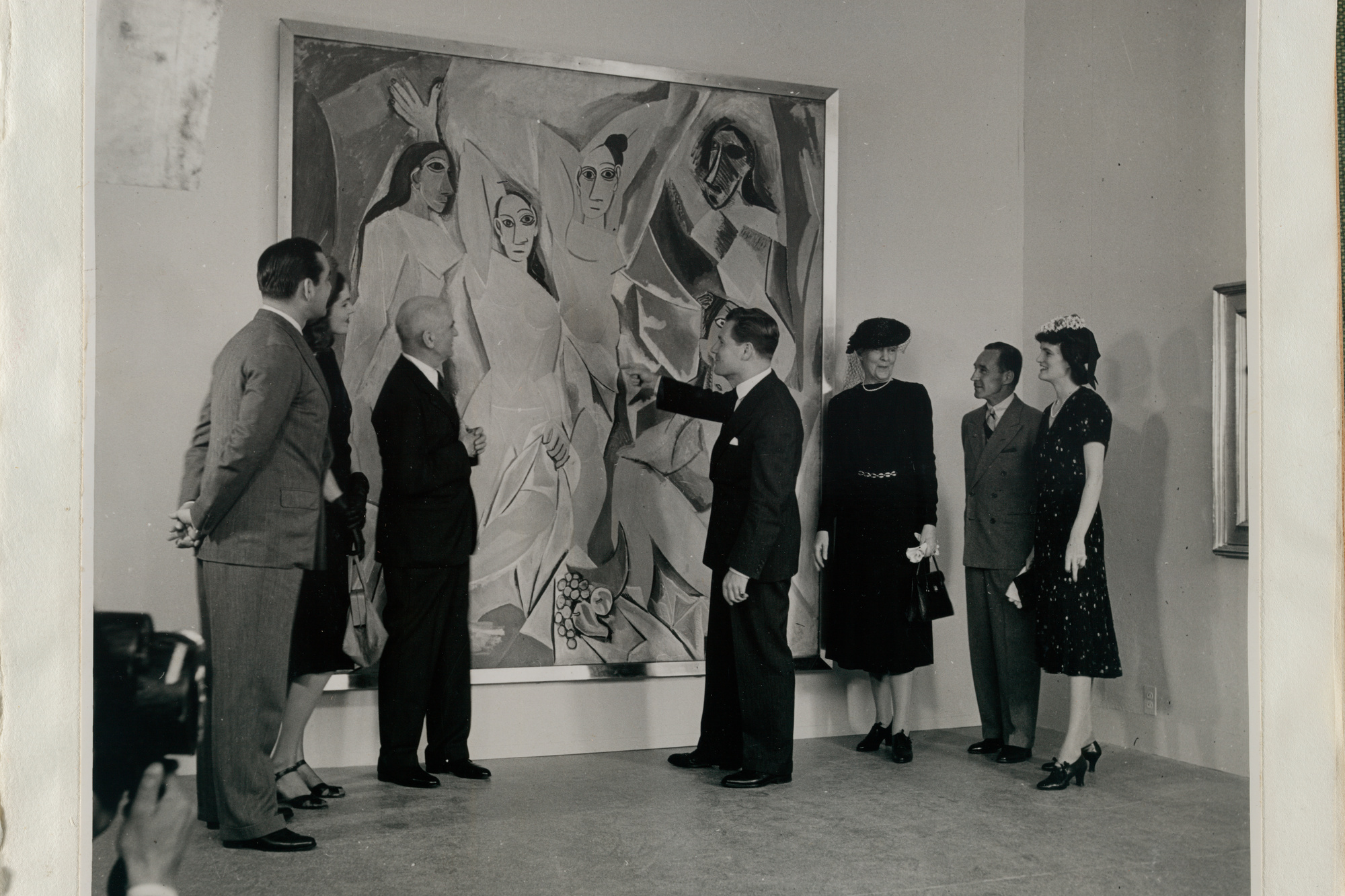 Pablo Picasso's *Les Demoiselles d'Avignon (1907), upon its acquisition. From left: John Hay Whitney, Lily Emmet Cushing, A. Conger Goodyear, Nelson A. Rockefeller, Jeanie Sheppard, Edsel Ford, and Elizabeth Bliss Parkinson. 1939. A. Conger Goodyear Scrapbooks, 52