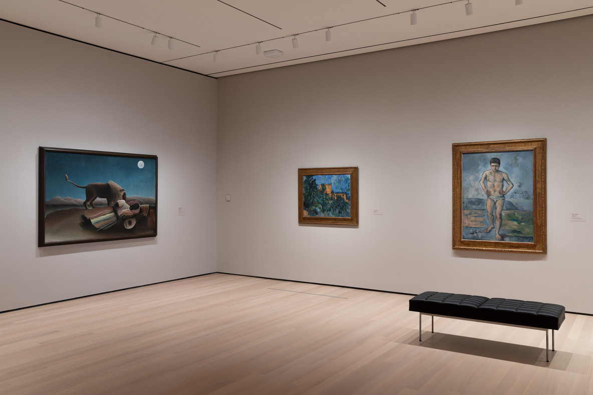 An installation view of Gallery 501. From left: Henri Rousseau's The Sleeping Gypsy (1897) and Paul Cézanne's Château Noir (1903–04) and The Bather (c. 1885)