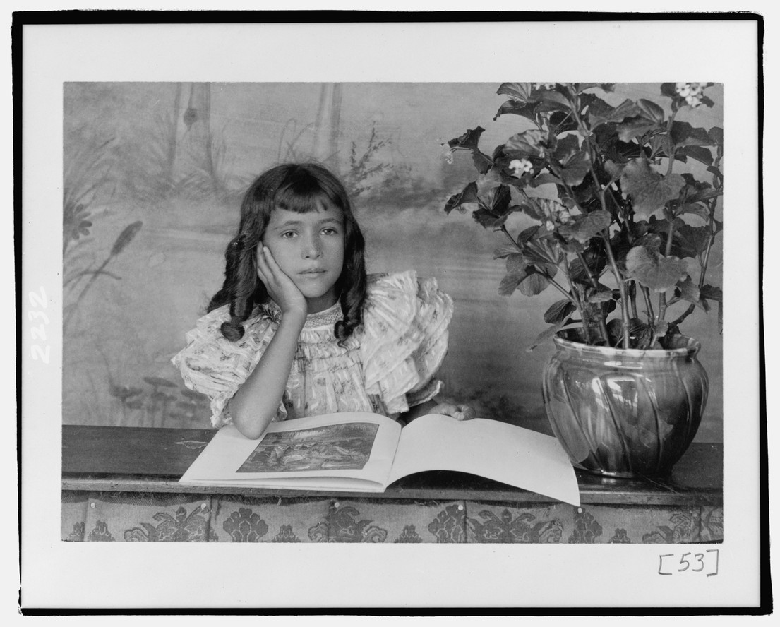 A photo featured in Wayward Lives, Beautiful Experiments: Thomas E. Askew. African American girl, half-length portrait, with the right hand to cheek, with illustrated book on table. c. 1900