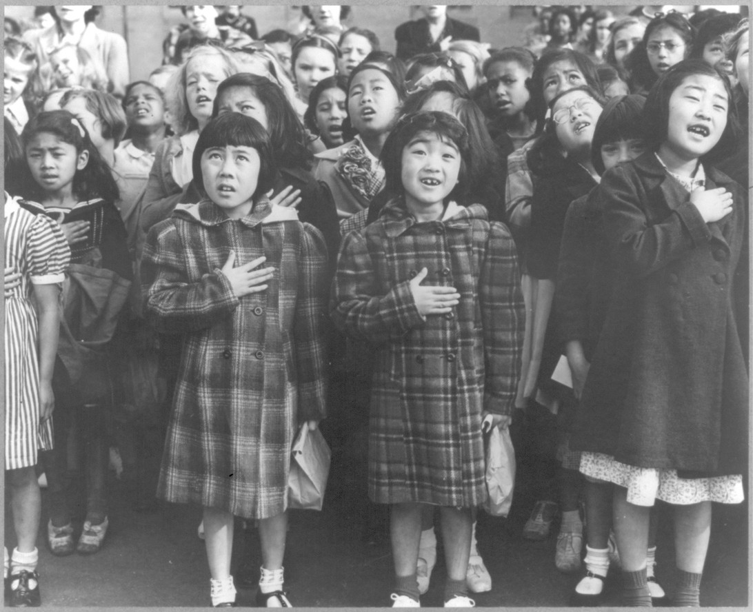 "Dorothea Lange. ""San Francisco, Calif., April 1942 - Children of the Weill public school, from the so-called international settlement, shown in a flag pledge ceremony. Some of them are evacuees of Japanese ancestry who will be housed in War relocation authority centers for the duration."""