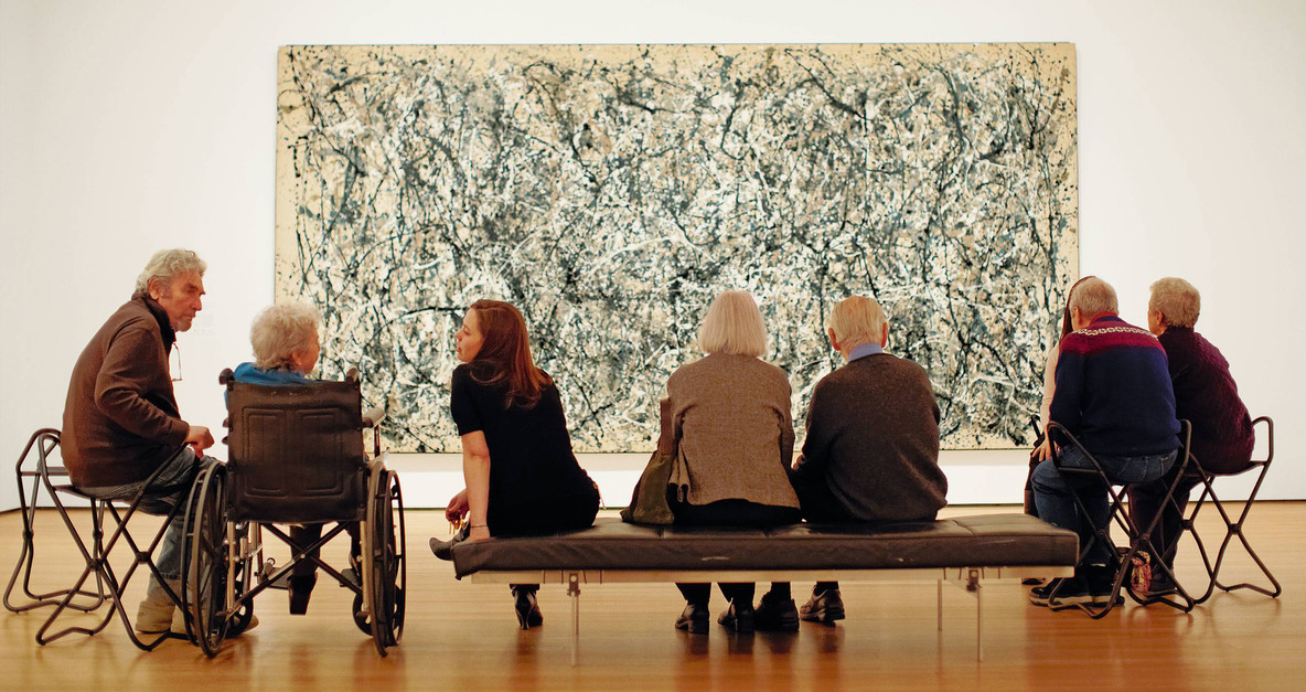"Older adults take in a Jackson Pollock during a MoMA Access Program. From ""For Caregivers: A Guide for Connecting Creatively."" Image description: In a gallery, a group of seven adults sits with their backs to the camera, in front of a large abstract painting. Most of the adults have gray hair. One adult with long light brown hair is turned to the left, speaking to a gray-haired individual in a wheelchair. In the background, the painting, so large it is only partially visible, features arcing spatters of black, white, and gray paint."