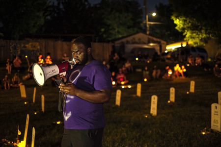 A young man reads out the names of police violence victims—those also present on the makeshift tombstones in the park—aloud to a crowd in Powderhorn, Minneapolis. Picture and caption by Laylah Amatullah Barrayn © 2020