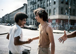 Meryl Meisler. Handshake. 1984. Image courtesy of the artist. Alt text: Two young men with mustaches shake each others hand in greeting on a New York City street. The man on the left wears a white t-shirt and holds a silver boombox. The man on the right wears a beige tank top tucked into slim khaki pants with a silver chain necklace around his neck. On the right side of the photograph, an outstretched hand reaches towards them from outside of the frame.