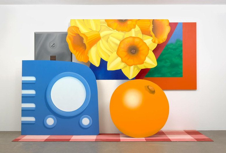Tom Wesselmann. Still Life #57. 1969–70. Oil on canvas and base of acrylic paint on carpet, in six sections. Gift of the artist. © Tom Wesselmann/Licensed by VAGA, New York, NY Alt Text: A gallery installation view of five shaped paintings arranged as larger than life sized objects placed on a red checkered picnic blanket. On the left is a periwinkle blue radio, with four lighter blue buttons on the left side and a large circular speaker in the center with two small knobs below. Behind it is a silver metallic switch plate. In the back center is a blue and white vase holding a spray of yellow daffodils. To the right of the flowers is a red-framed window in the shape of an acute triangle, with an abstracted blue and green landscape. Below the window and flowers is an orange, with the navel facing up at the one o'clock position.