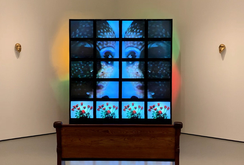 Theo Eshetu. Till Death Do Us Part. 1982–87. Two-channel video (color, sound; duration variable), 20 monitors, two clay masks, disco lights, and pew. Courtesy the artist. © 2020 Theo Eshetu. Digital image © 2020 The Museum of Modern Art, New York. Photo: Stuart Comer