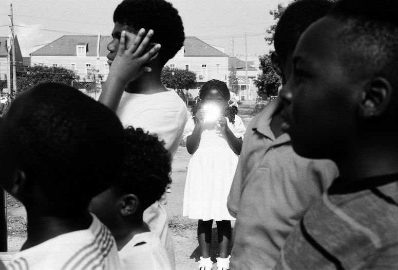 Garrett Bradley. America. 2019. Multichannel video installation. Courtesy the artist. Caption: A black-and-white image of a young Black girl in a white dress holding a reflective object that hides her face. Alt-text: Garrett Bradley. America. 2019. Multichannel video installation. Courtesy the artist. Image Description: A black-and-white image of a young Black girl stands in the background of three young Black boys in front of her, to the left, and facing left, and two Black boys in front of her, to her right, facing left, wearing grey polos and white striped tee shirts. She is facing and looking directly at the camera. She is standing in a white dress with puffed short-sleeves and socks with ruffle ankle socks poking out of the tops of her black patent leather mary janes. Her hair is pulled into two ponytails by her ears with white ribbons. She is holding an object to her chest, that is reflecting light or possibly a camera flash.