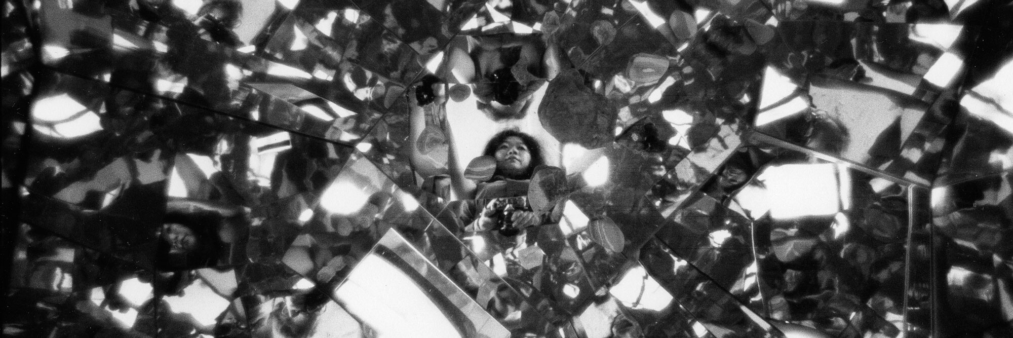 Peter Moore. Photograph of Shigeko Kubota reflected in Three Mountains (1976–79) in her loft on Mercer Street, New York, 1979. Courtesy Shigeko Kubota Video Art Foundation. Photo © 2021 Barbara Moore/Licensed by VAGA at Artists Rights Society (ARS), NY. Courtesy Paula Cooper Gallery, New York. Shown: Shigeko Kubota. Three Mountains. 1976–79. Four-channel standard-definition video (color, sound; approx. 30 min. each), seven cathode-ray tube monitors, plywood, and mirrors, overall dimensions variable. © 2021 Estate of Shigeko Kubota/Licensed by VAGA at Artists Rights Society (ARS), NY
