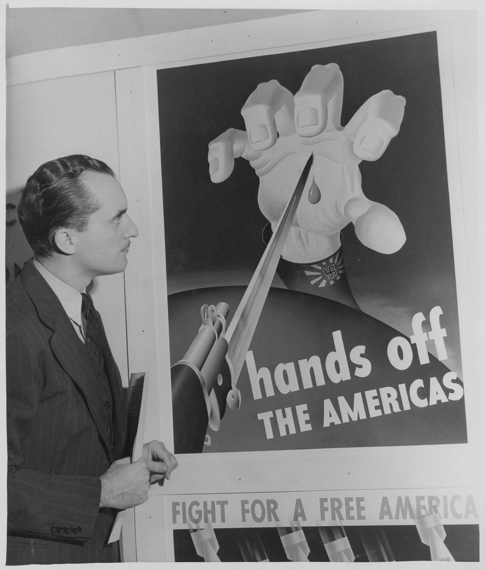 "Unidentified man at the exhibition, ""United Hemisphere Poster Competition."" October 21, 1942–November 24, 1942. Photographic Archive. The Museum of Modern Art Archives, New York. IN201.1. Photograph by Phil Caputo."