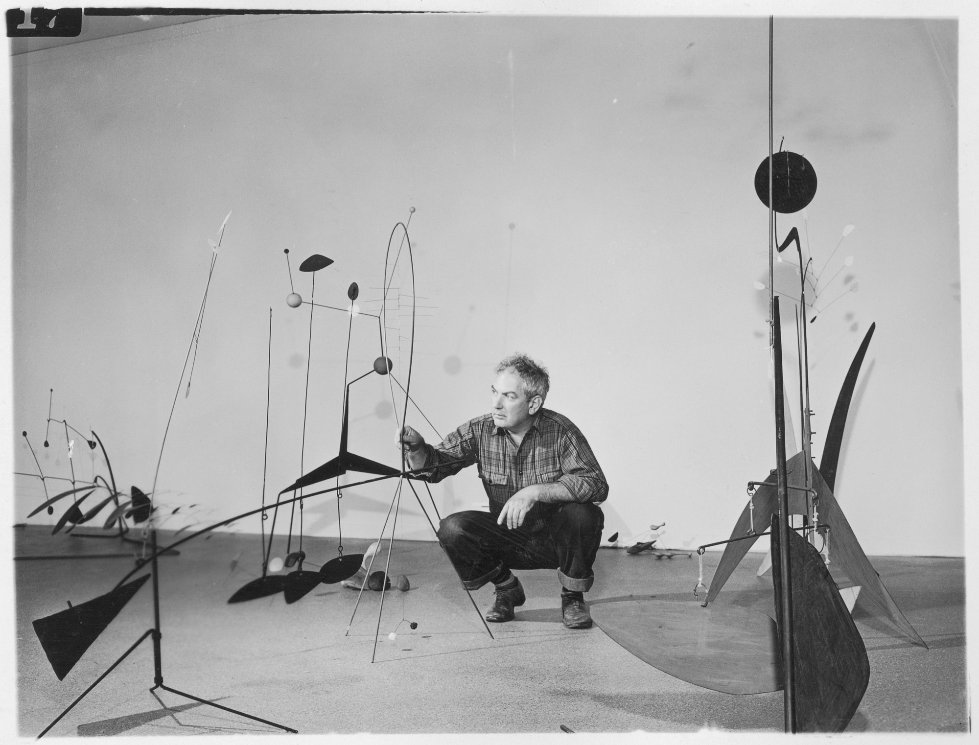 """Alexander Calder, American Sculptor and Constructivist, arranges a few of his mobiles in the big exhibition of his work which opens at the Museum of Modern Art, 11 West 53 Street, on Wednesday, September 29. Nearly 100 mobiles, stabiles, constellations and pieces of jewelry will be shown. Mr. Calder was born near Philadelphia and lives in Roxbury, Connecticut, and New York City."" September 29, 1943–January 16, 1944. Photographic Archive. The Museum of Modern Art Archives, New York. IN242.2"