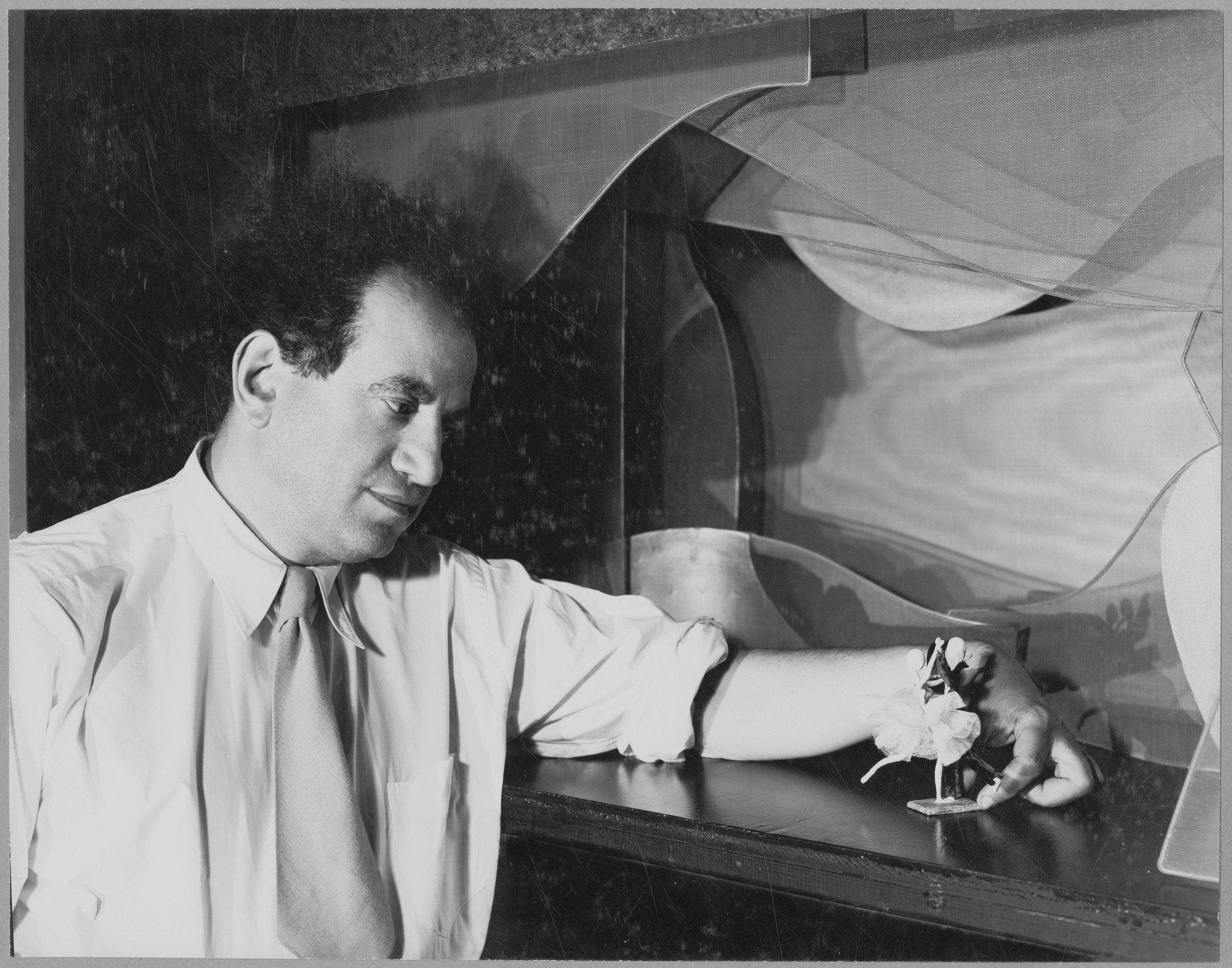 """Boris Aronson with his model stage for projected scenery, 1947,"" at the exhibition, ""Boris Aronson:  Stage Designs and Models."" June 24, 1947–October 10, 1947. Photographic Archive. The Museum of Modern Art Archives, New York. IN354.1. Photograph by Soichi Sunami."