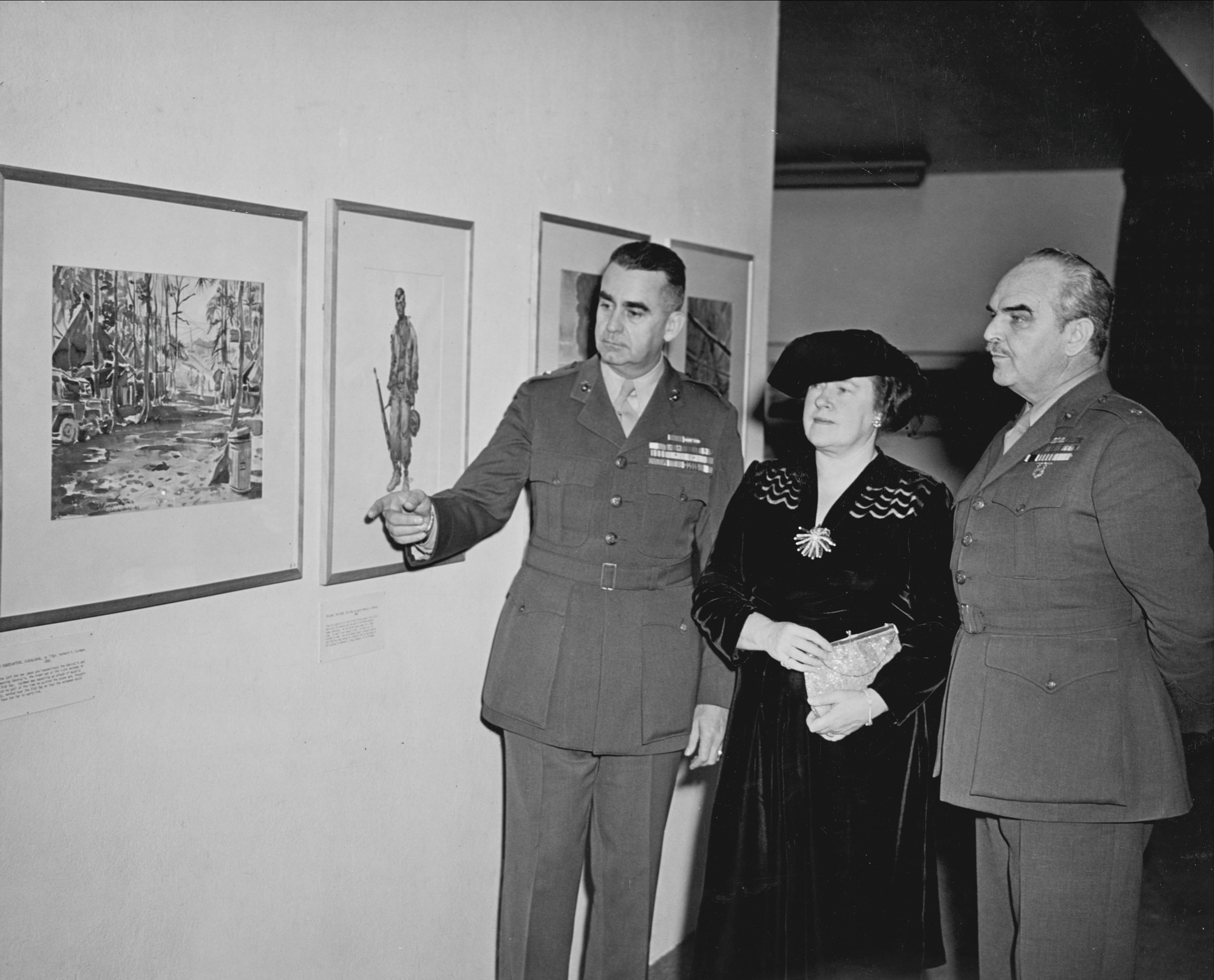 """Brigadier General del Valle and Mrs. del Valle visit 'Marines under Fire' Exhibition.  Brigadier General Pedro Augusto del Valle, U.S.M.C. and Mrs del Valle are shown looking at T/Sgt. Herbert Hugh Laidman's watercolor 'Wing Headquarters, Guadalcanal' in the exhibition of 'Marines under Fire' at the Museum of Modern Art (November 10 - January 9).  General del Valle was at Guadalcanal and most of the scenes portrayed in the exhibition are very familiar to him."" November 10, 1943–January 9, 1944. Photographic Archive. The Museum of Modern Art Archives, New York. IN245.1"