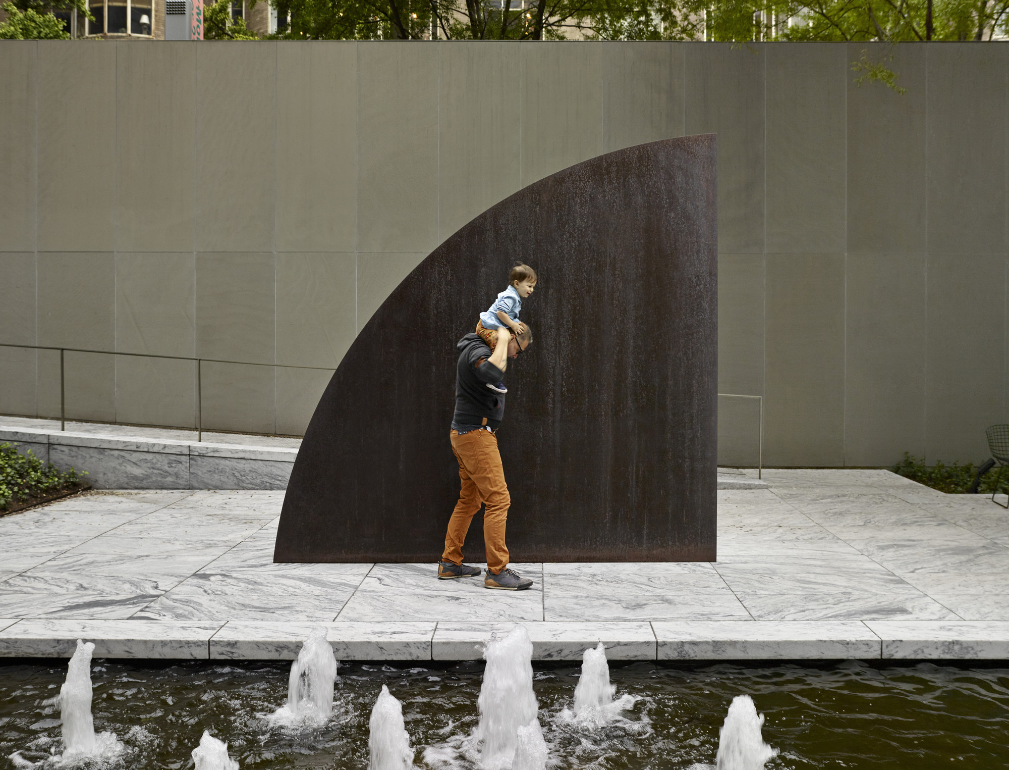 A view of the Abby Aldrich Rockefeller Sculpture Garden. Shown: Ellsworth Kelly. Curve II. 1973. Weathering steel. The Museum of Modern Art, New York. Gift of Philip Johnson. © 2020 Ellsworth Kelly Photo: Noah Kalina