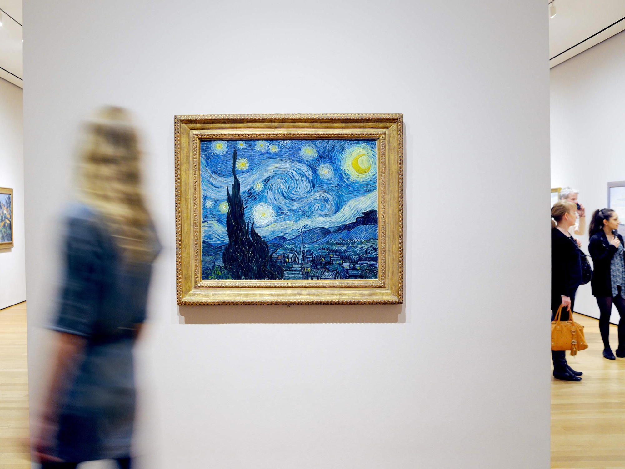 Visitors in the galleries. Shown: Vincent van Gogh. The Starry Night. 1889. Oil on canvas. Acquired through the Lillie P. Bliss Bequest. © 2017 The Museum of Modern Art. Photo: Martin Seck