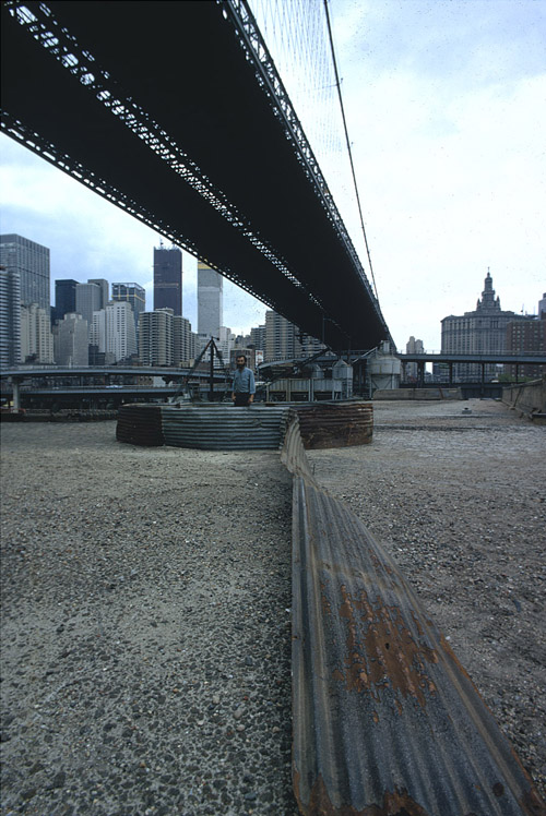 Richard Nonas with his installation beneath the Brooklyn Bridge. Unknown photographer. The Brooklyn Bridge Event, N.Y., N.Y. (May 24, 1971). Color slide. MoMA PS1, 2462. The Museum of Modern Art Archives, New York.