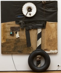 "Robert Rauschenberg, <em>First Landing Jump</em> 1961. Cloth, metal, leather, electric fixture, cable, and oil paint on composition board, with automobile tire and wood plank, 7' 5 1/8"" x 6' x 8 7/8"" (226.3 x 182.8 x 22.5 cm). Gift of Philip Johnson"