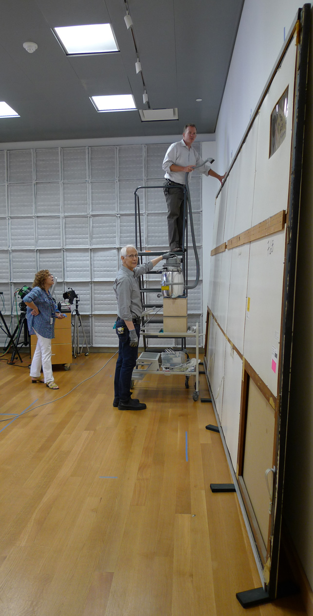 Paintings conservator Michael Duffy, on ladder, removes loose dust from the top edge of One: Number 31, 1950, and the first panels of the painting's protective backing are removed