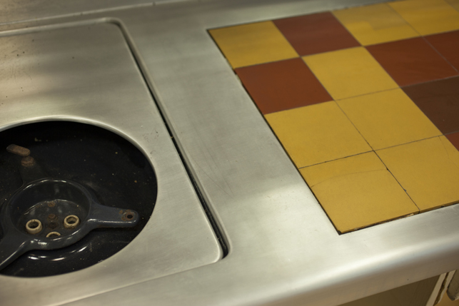 A detail of the bent and welded aluminum sheet countertop. The surface was polished to reduce the appearance of the welding lines. One can be seen running in-between the stove and the ceramic tiles.