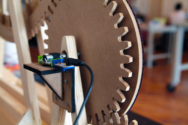 The Midown Design Store features a big wheel, which is propelled by a miniature cyclist, furiously pedaling ahead. His wheel is powered by a DC motor Bit, which is located behind the center wheel and pictured here. The motor controls a series of gears that create a spinning ferris wheel, aglow with LED lights.