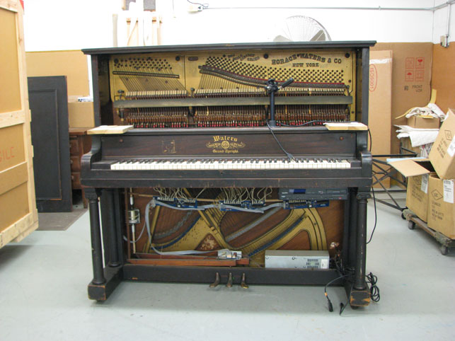 Original piano player unit and exposed circuitry under the keyboard