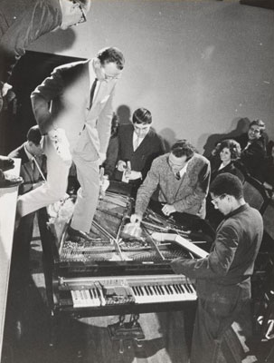 "Philip Corner with Emmett Williams, George Maciunas, Benjamin Patterson, Dick Higgins, and Alison Knowles. Piano Activities, performed during Fluxus Internationale Festpiele Neuester Musik, Hörsaal des Städtischen Museums, Wiesbaden, Germany, September 1, 1962. Gelatin silver print, 8 1/4 x 6 5/16"" (20.9 x 16 cm). Original photographer: Deutsche Presse Agentur. The Gilbert and Lila Silverman Fluxus Collection Gift. Photo: Peter Butler"