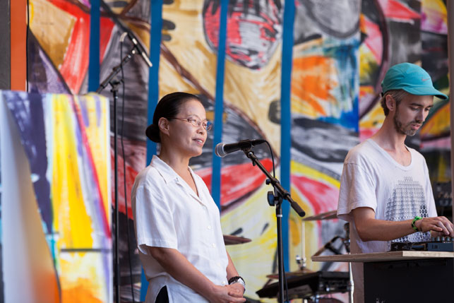 Terreke greets the early afternoon crowd with some guidance from Dr. Ven. Chung Ohun Lee. MoMA PS1 Warm Up, Saturday, 24, 2013. Photo: Zachary Newton