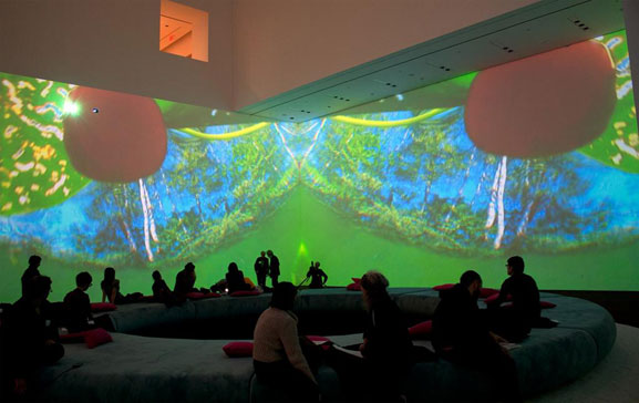Pipilotti Rist. Pour Your Body Out (7354 Cubic Meters). 2008. Multichannel video projection (color, sound), projector enclosures, circular seating element, carpet. Installation view, The Museum of Modern Art, November 19, 2008–February 2, 2009. Courtesy the artist, Luhring Augustine, New York, and Hauser & Wirth Zürich London