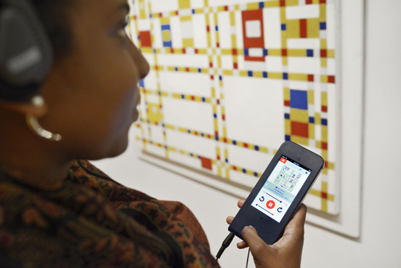 A visitor in the galleries using the MoMA Audio+ mobile