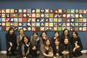 Participants in the professional exchange in front of artwork created in workshops